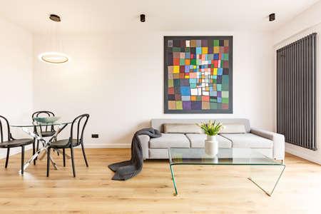 Blumen auf Glastisch im Innenraum der Wohnung mit Malerei über grauem Sofa nahe schwarzen Stühlen. Echtes Foto
