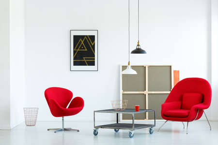 Real photo of a modern living room interior with red armchairs, movable coffee table, canvas and lamps Reklamní fotografie