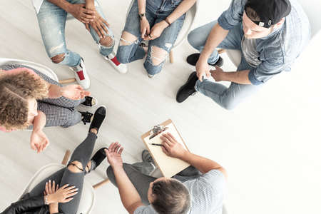 Top view of a psychotherapist working with a group of difficult teenagers in an anger management class Foto de archivo - 104071298