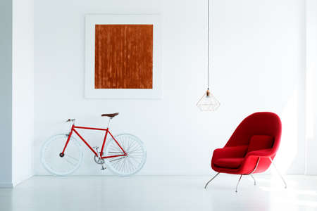 Bike and red armchair set on a white wall with a simple painting and lamp Stock Photo