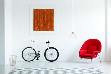 Real photo of a bike with black tires, red armchair, painting and patterned rug in an anteroom interior