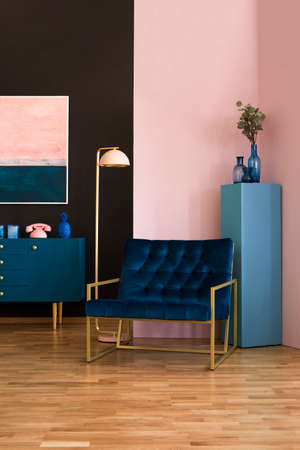 Lamp next to navy blue armchair in elegant living room interior with painting above cabinet Banque d'images - 104116382