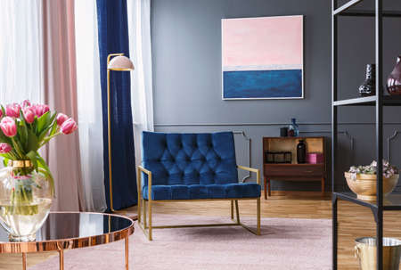 Navy blue armchair next to lamp in sophisticated apartment interior with painting and flowers. Real photo