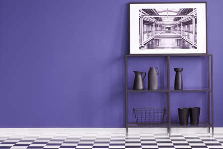 Black shelf with decorations, poster on a purple wall and geometrical floor in creative interior. Place for your furniture