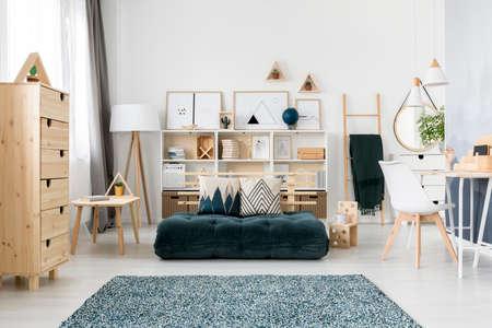 Materasso piegato verde e cuscini con motivo collocato all'interno del soggiorno scandinavo con mobili in legno e galleria semplice