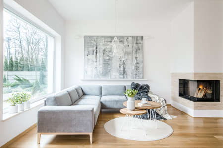 Two hairpin tables with books, tulips and coffee cup placed on a white rug in bright living room interior with grey sofa, fireplace and abstract painting on the wall