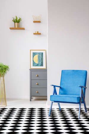 Open space room interior with linoleum checkerboard floor, blue armchair, fresh plants and poster standing on grey cupboard