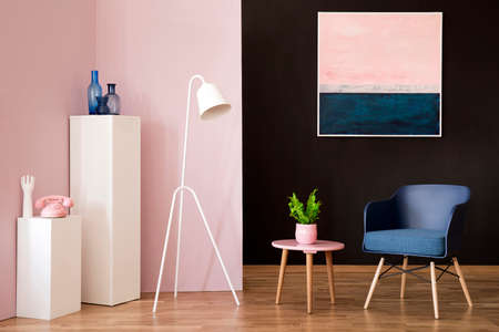 White lamp next to a pink table with plant and navy blue armchair in vintage living room interior