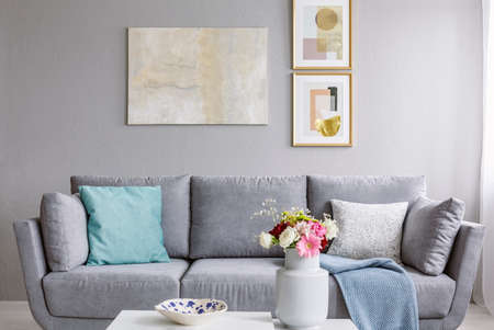 Modern painting and two gold posters hanging on the wall in grey sitting room interior with sofa with pillows and fresh colorful flowers in ceramic vase