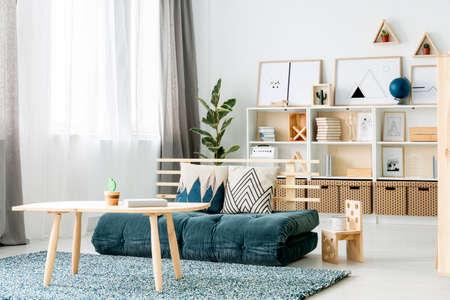 Sofá colchón verde oscuro con dos cojines decorativos colocados en el interior de la habitación de niña de estilo nórdico con ventanas y estante de madera con libros y carteles