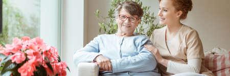 Cuidador profesional con su cargo senior sentada en un sofá en una luminosa sala de estar en una casa de vida asistida. Flores florecientes en un alféizar de la ventana. Panorama. Foto de archivo