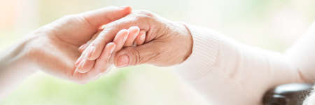 Close-up of tender gesture between two generations. Young woman holding hands with a senior lady. Blurred background. Panorama. 写真素材