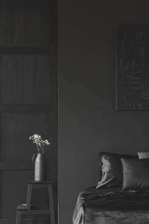 Flowers on a stool next to bed in simple black bedroom interior with dark poster 版權商用圖片