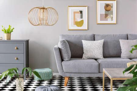 Zwei gemusterte Kissen auf grauem Sofa im hellen Wohnzimmer mit frischen Pflanzen, Holzschrank, goldener Lampe und zwei einfachen Postern an der Wand Standard-Bild