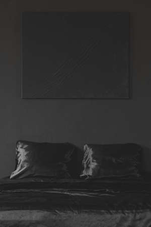 Black poster above bed in minimal monochromatic bedroom interior 版權商用圖片