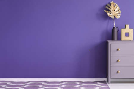 Purple empty wall in a room interior with a chest of drawers with vases, golden leaf, and patterned carpet Stock Photo