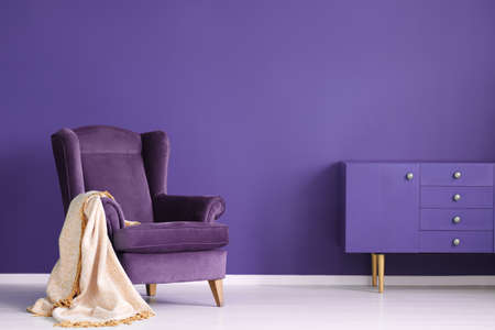 Vintage armchair, beige blanket and cabinet set on a violet wall in a living room interior Stock Photo