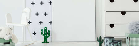 Wooden rocking horse in bright baby room interior with decorative cactuses, white cupboard, and empty poster on the floor. Paste your graphic here