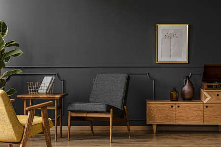 Wooden furniture in vintage room interior with black walls with molding and dark armchair