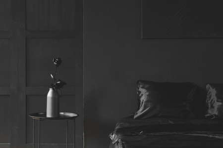 Rose in vase on a table next to bed against dark wall with poster in black bedroom interior 写真素材 - 104117613