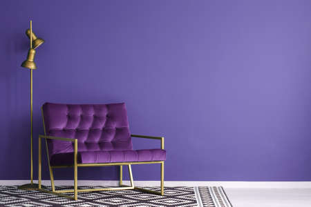 Ultra violet armchair with golden details and lamp standing on the empty wall in living room interior