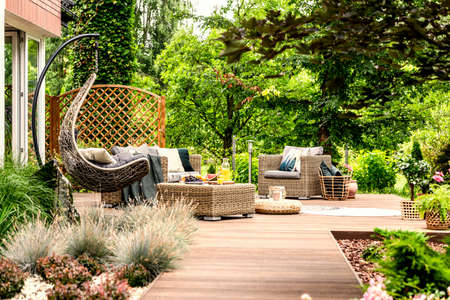 Single swing and garden furniture set on a wooden terrace in a green garden with trees and bushes