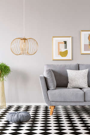 Pillow placed on the checkerboard linoleum floor in grey sitting room interior with gold lamp, couch with pillow and two modern posters hanging on the wall