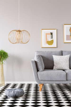 Almohada colocada en el piso de linóleo de tablero de ajedrez en el interior de la sala de estar gris con lámpara de oro, sofá con almohada y dos carteles modernos colgados en la pared Foto de archivo
