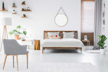 Gray, modern armchair, breakfast tray on a double bed and wooden furniture in a simple, stylish apartment room interior with white walls Archivio Fotografico