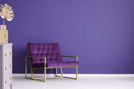 Wide armchair, chest of drawers and golden decorations set on a purple, empty wall in living room interior. Place your product