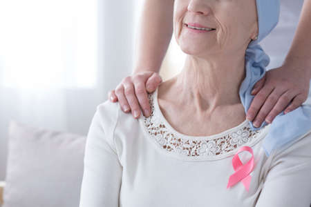 Close-up of hands on a smiling woman's shoulders who is wearing breast cancer ribbon
