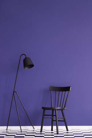 Black lamp and chair set on a violet wall in simple living room interior. Place your product