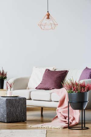 Nahaufnahme von Heidekraut in schwarzer Vase neben Sofa und grauem Hocker im Wohnzimmerinnenraum mit Kupferlampe Standard-Bild