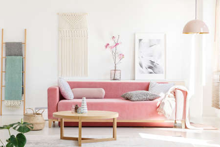 Real photo of a pink sofa with cushions and blanket standing behind a wooden table in bright living room interior with a hanging lamp, ladder, poster and flowers 版權商用圖片 - 104189103