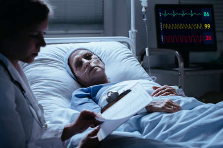 Sick elderly woman with cancer looking at doctor with test results during visit Stock fotó - 104167377
