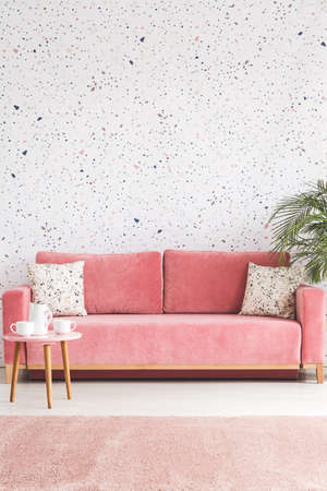 Pillows on pink sofa against lastrico wallpaper in living room interior with table and plant. Real photo