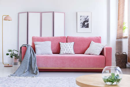Real photo of a pink couch with white pillows and a blanket standing in a cozy living room interior with a table, a vase, a lamp and a screen Stock Photo