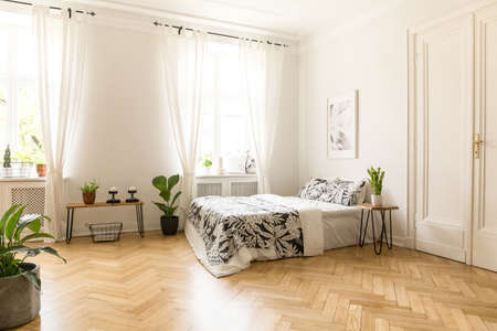 Patterned sheets on bed under poster in spacious bright bedroom interior with plants. Real photo