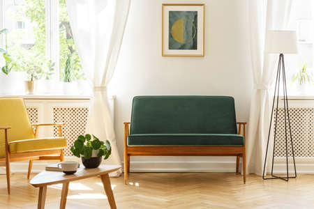 Poster above green bench between lamp and yellow armchair in vintage living room interior. Real photo