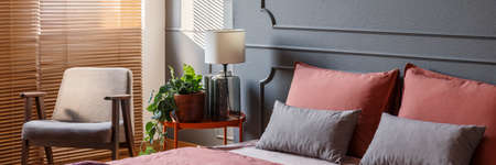 Orange metal bedside table with glass lamp and fresh plant, grey and pink pillows on bed and armchair standing by the window with wooden blinds in bedroom interior