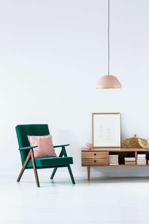 Green armchair with pink pillow next to a wooden cupboard in living room interior with poster