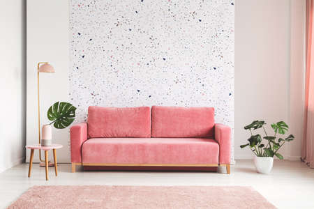 Sofá rosa entre planta y lámpara en el interior luminoso de la sala de estar con paredes estampadas. Foto real