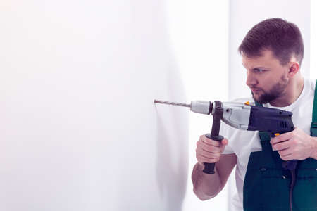 Professional construction worker with drill making a hole in white wall Фото со стока