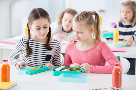 Two young girls during snack time in a school looking into each other's lunch boxes with healthy vegetables and bread. Bottles of fruit juices on the desk. Other kids in blurred background Stockfoto