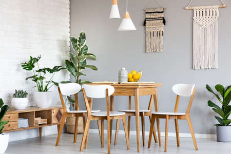 Macrame hanging on gray wall above wooden table and chairs in bright dining room interior with lots of plants. Real photo
