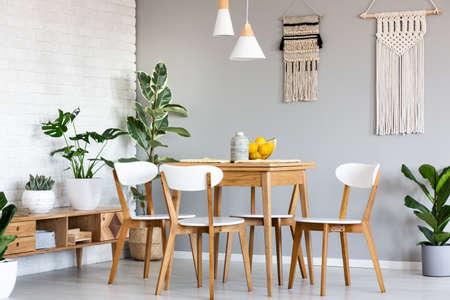 Macrame opknoping op grijze muur boven houten tafel en stoelen in lichte eetkamer interieur met veel planten. Echte foto Stockfoto