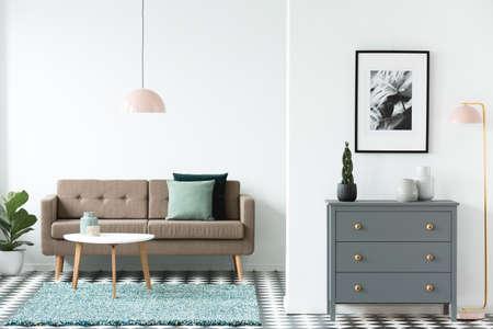 Sofá marrón con cojines verdes de pie en el interior de la sala de estar de espacio abierto blanco con mesa de madera en la alfombra, armario gris, cartel simple y lámparas de color rosa pastel