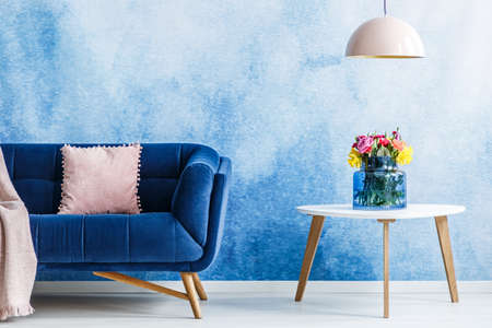 Comfortable plush settee with pastel cushion and a side table with fresh flowers in a vase against blue and white ombre wall in a living room interior. Lamp hanging over the table. Real photo.