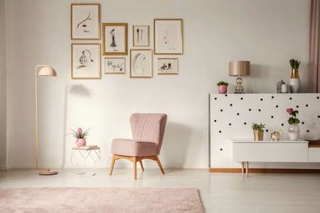 Old-fashioned armchair, pastel pink floor lamp and stylish, golden decorations in a retro living room interior with white walls