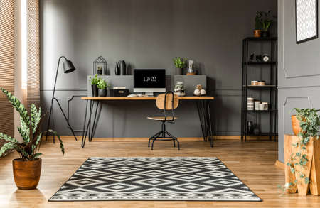Patterned Carpet And Plants In Scandi Grey Home Office Interior With Wooden  Chair At Desk Stock